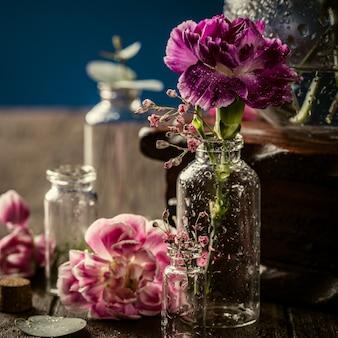 Bellissimo garofano viola in vaso di vetro sulla superficie blu scuro. festa della mamma, biglietto di auguri di compleanno. copia spazio