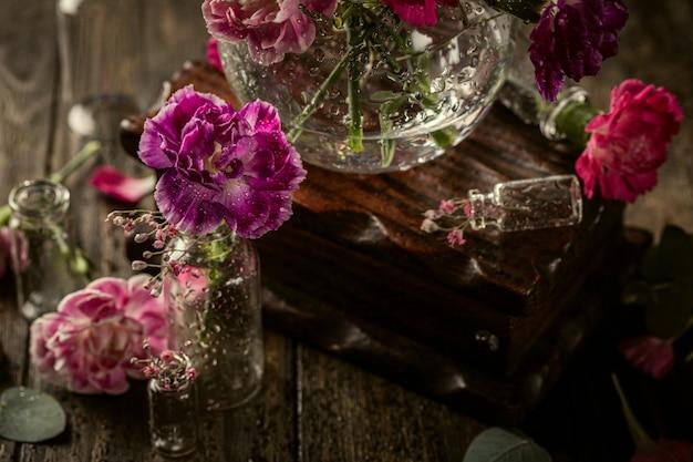 Bellissimo garofano viola in vaso di vetro sulla superficie blu scuro. festa della mamma, biglietto di auguri di compleanno
