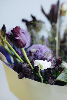 Bellissimo bouquet di fiori viola sullo sfondo del muro grigio, vista laterale di consegna del negozio di fiori moderno verticale