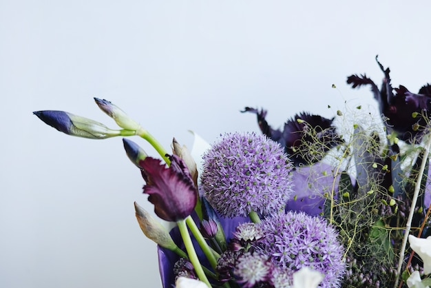 Bellissimo bouquet di fiori viola sullo sfondo del muro grigio, vista laterale di consegna del negozio di fiori moderno