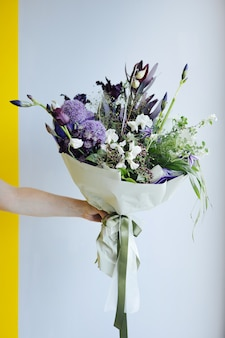 Bellissimo bouquet di fiori viola nelle mani sullo sfondo del muro grigio, vista laterale di consegna del negozio di fiori moderno