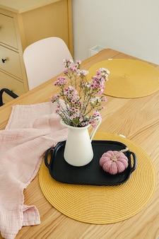 Bellissimo bouquet di fiori viola in una brocca bianca sul piatto di legno. all'interno di un moderno appartamento in stile scandinavo. il concetto di comfort domestico
