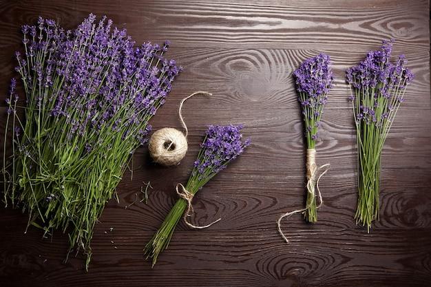 Bellissimi mazzi di fiori di lavanda viola su fondo di legno scuro, vista dall'alto