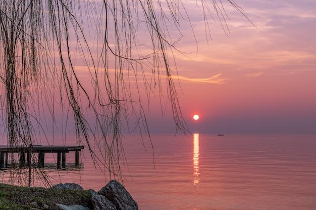 Bellissimo tramonto viola durante la nebbia sul lago di garda con la sagoma di una barca di pescatori sullo sfondo