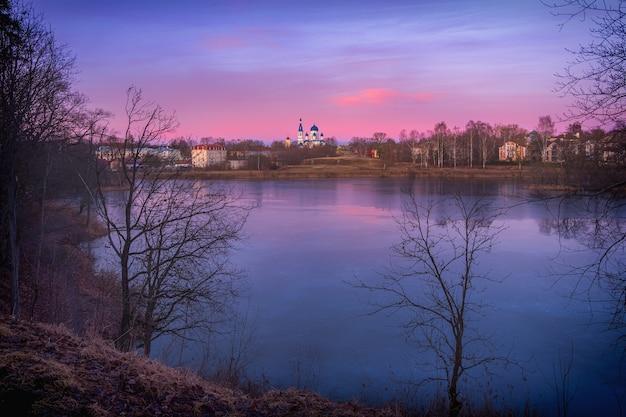 Bel tramonto viola sul lago. il tempio sulla collina. l'antica città russa di gatcina
