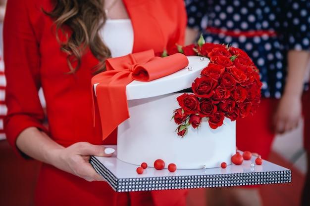Bella torta rossa con fiocco e rose tenere nelle mani.