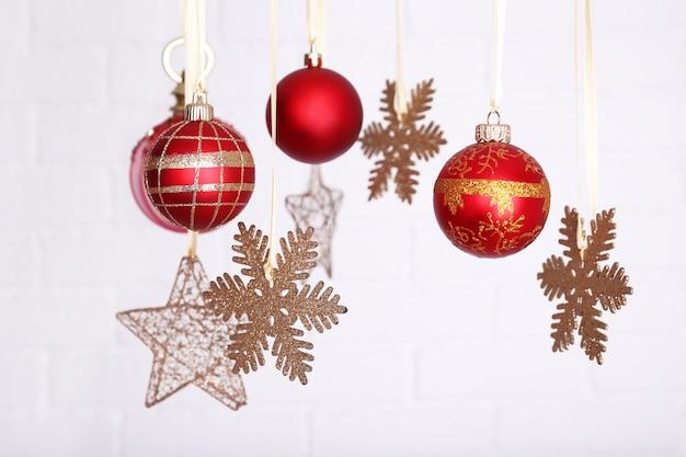 Bellissime decorazioni natalizie rosse appese su uno sfondo sfocato chiaro
