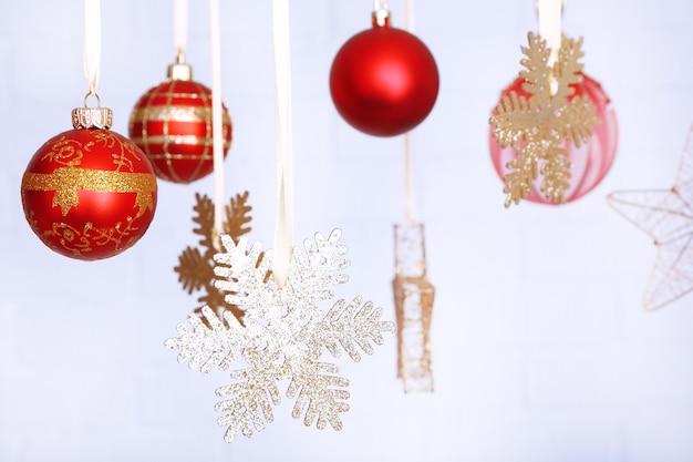 Bellissime decorazioni natalizie rosse appese su una superficie sfocata leggera