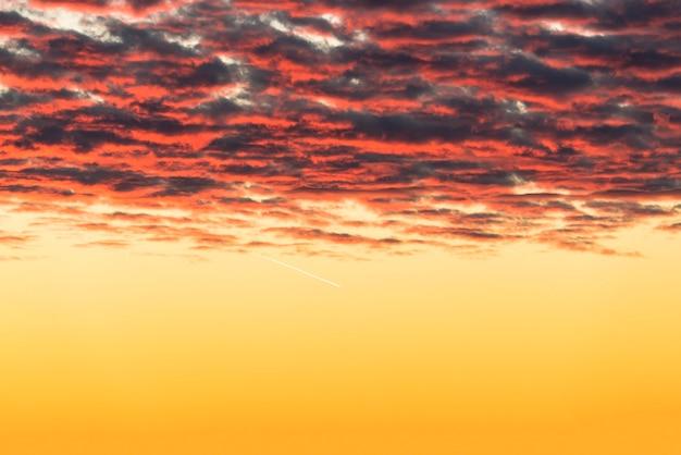 Bellissime nuvole rosse illuminate dai raggi del sole al tramonto fluttuano nel cielo giallo oro.