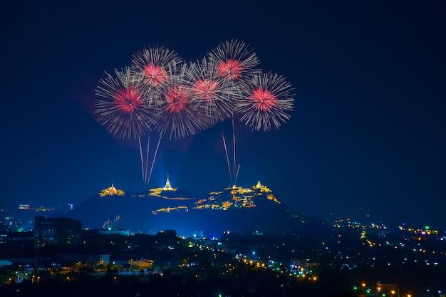 Bei fuochi d'artificio rossi alla notte con il tempio sul mountain view