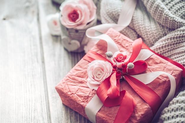 Bellissimo contenitore di regalo rosso sulla parete di legno