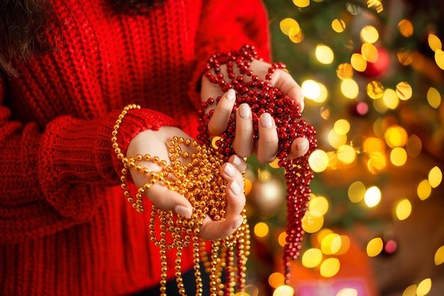 Bello primo piano rosso e dorato dei branelli nelle mani di una giovane ragazza