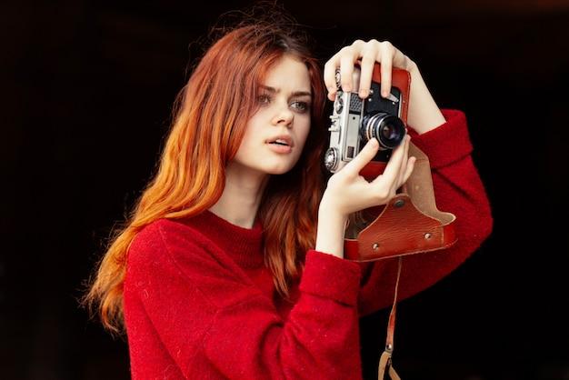 Il bello fotografo femminile dai capelli rossi scatta le foto con una vecchia macchina fotografica