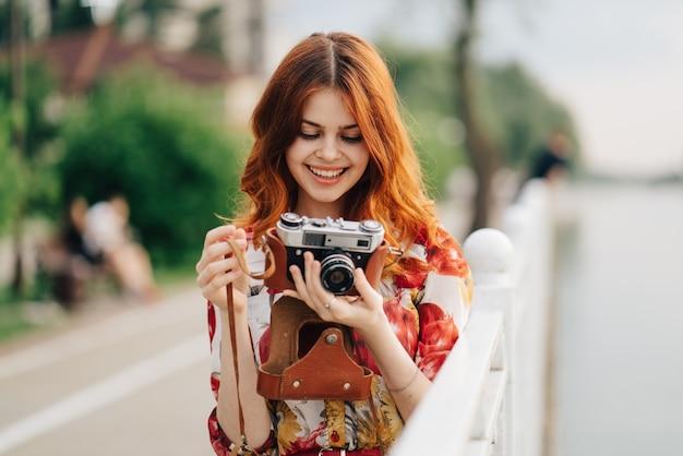 Bella fotografa dai capelli rossi scatta foto con una vecchia macchina fotografica