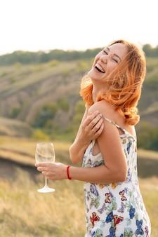 Bella ragazza dai capelli rossi si diverte e balla in un campo al tramonto.