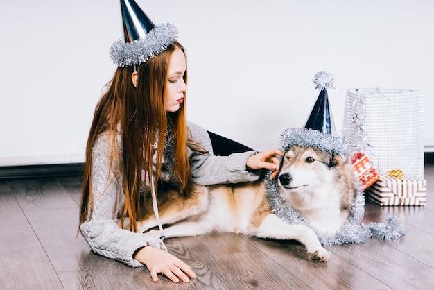 La bella ragazza dai capelli rossi giace sul pavimento con il suo grosso cane che festeggia il nuovo anno