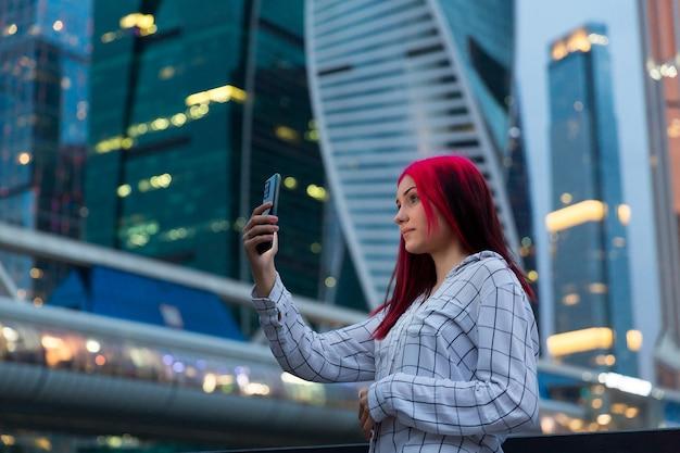 Bella ragazza dai capelli rossi che fa selfie su smartphone la sera sulla strada della città illuminata.