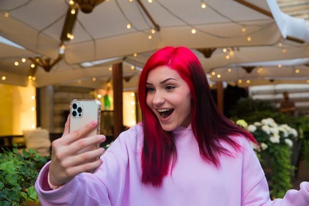 Bella ragazza blogger influencer dai capelli rossi al bar che parla facendo videochiamate utilizzando lo smartphone con i suoi abbonati nei social network.