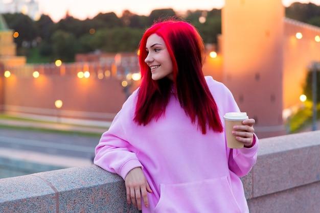Bella ragazza adolescente dai capelli rossi in felpa con cappuccio rosa che beve caffè la sera sulla strada illuminata della città.