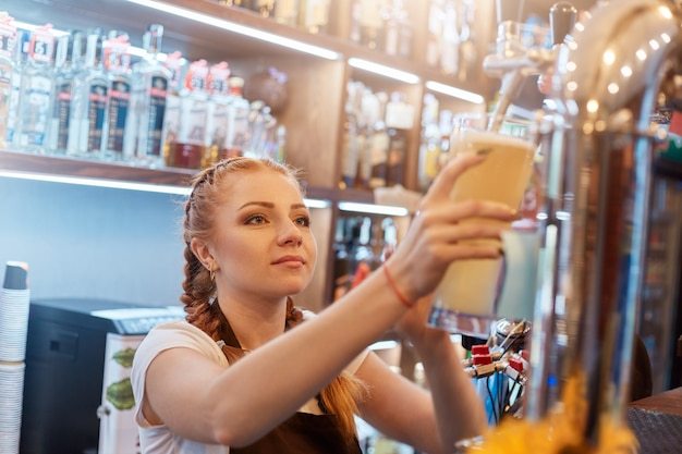 Bello cameriere dai capelli rossi che spunta birra nel bicchiere, guarda concentrato al rubinetto, indossa una maglietta casual bianca