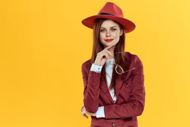 Bella donna dai capelli rossi in un tailleur e cappello rosso, immagine elegante ufficio