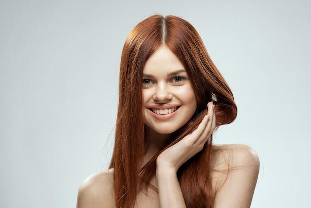 Bella donna dai capelli rossi con spalle nude e sfondo chiaro glamour capelli lunghi.