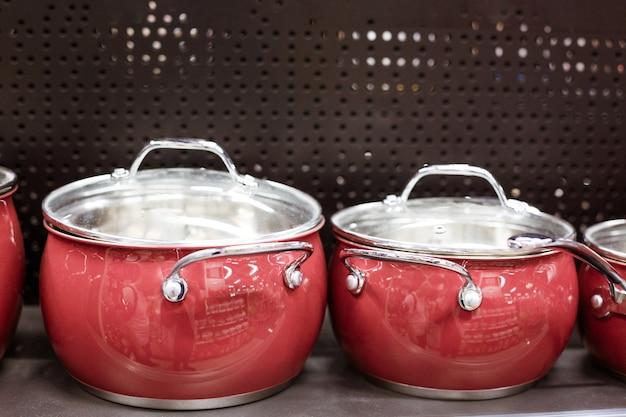 Belle padelle nuove rosse stanno su uno scaffale in un negozio, il concetto di acquisto di piatti