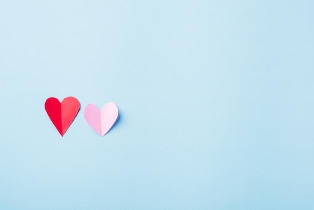 Bei cuori di carta rossi e rosa hanno tagliato la cartolina d'auguri della composizione
