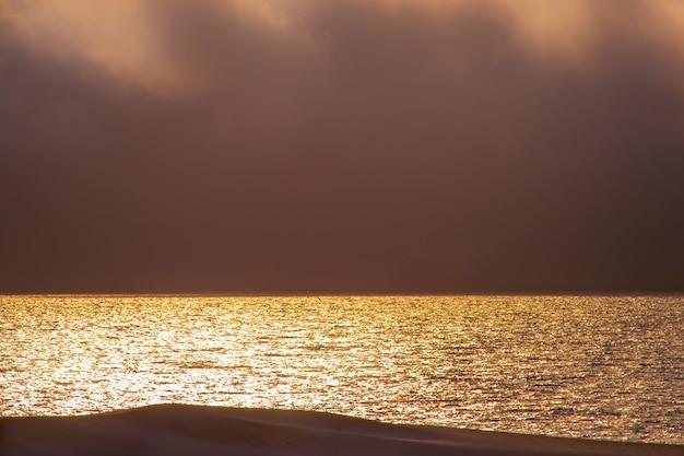 Bel tramonto rosso, nuvole scure e oceano atlantico all'orizzonte