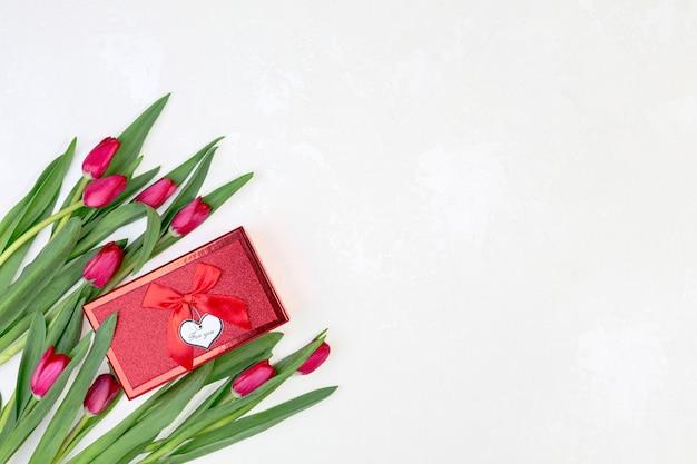 Bellissimi tulipani rossi e confezione regalo su uno sfondo bianco con texture con una copia dello spazio