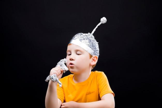 Un bellissimo ragazzo dai capelli rossi con un berretto fatto in casa fatto di un foglio di alluminio