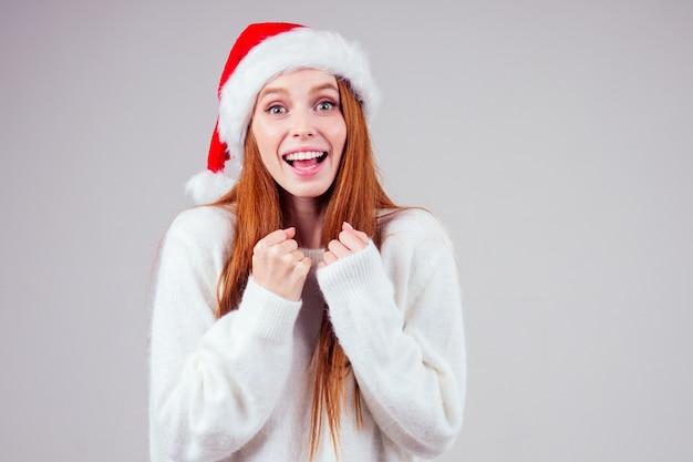 Bella donna dai capelli rossi allo zenzero bianco che indossa un maglione lavorato a maglia e cappello di babbo natale croce dito che esprime desideri