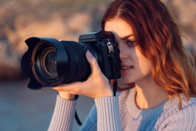 Bella donna dai capelli rossi con una macchina fotografica sulla natura nelle montagne vicino al fiume