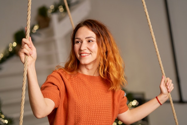 Una bella ragazza dai capelli rossi dondola nella sua stanza la notte di natale.