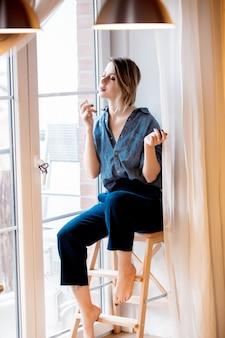 Bella ragazza rossa profumata di profumo e seduta su piccole scale a casa vicino alla finestra.