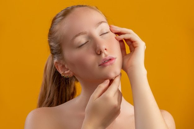 Bella donna rossa. crema idratante o primer viso. concetto di cura della gioventù e della pelle. trattamento facciale. concetto di bellezza, cosmetologia e cura della pelle. crema corporea.