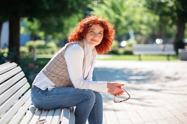 Bella donna rossa si siede su una panchina nel parco in una soleggiata giornata estiva e si gode la vita