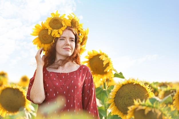 Bella donna dai capelli rossi nel campo di girasoli in giornata di sole