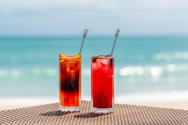 Bei cocktail di frutta rinfrescanti sul tavolo sul mare blu della spiaggia sullo sfondo
