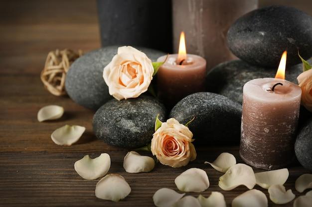 Bella composizione relax di candele accese, ciottoli e fiori su fondo in legno
