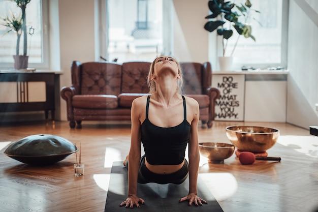Bella e rilassata donna in abiti neri fa yoga sul tappetino in postura bhujangasana in soggiorno con raggi di sole e design semplice.