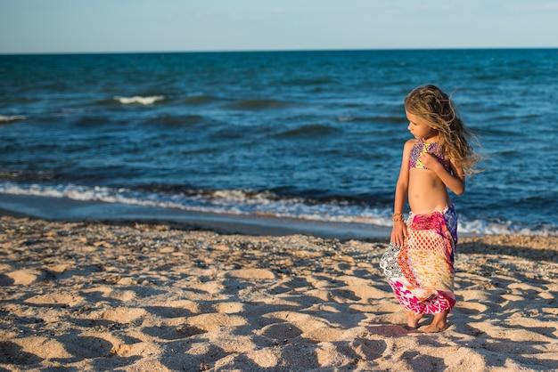 Bella donna rilassata che riposa sulla spiaggia in riva al mare con una sciarpa in una soleggiata giornata estiva calda.
