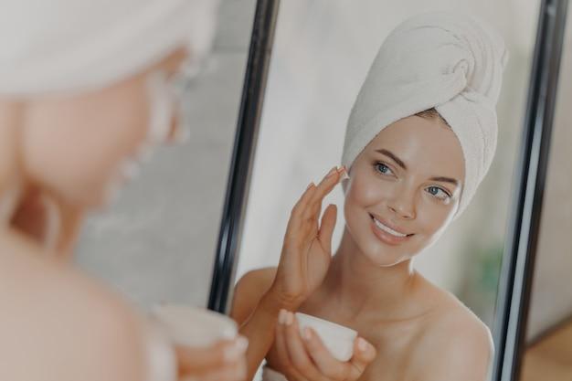 Bella donna rilassata avvolta in un asciugamano che applica la crema per il viso