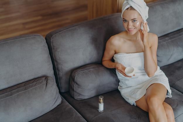 Bella donna rilassata avvolta in un asciugamano che beve il tè