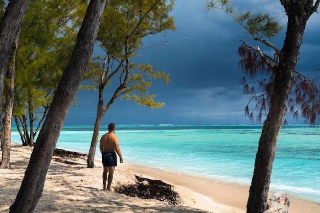 Un bel giovane rilassato in pantaloncini neri si trova sulla spiaggia dell'isola di mauritius.