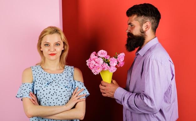Bella coppia romantica. fidanzato con fiori per fidanzata. bell'uomo barbuto con bouquet di rose per donna.
