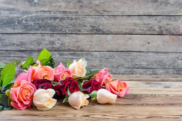 Belle rose sulla vecchia tavola di legno