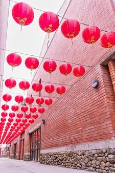 Bella lanterna rossa rotonda che appende sulla vecchia via tradizionale, concetto del festival lunare cinese del nuovo anno, fine su. la parola sottostante significa benedizione.