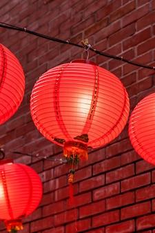 Bella lanterna rossa rotonda che appende sulla vecchia via tradizionale, concetto del festival lunare cinese del nuovo anno, fine su.