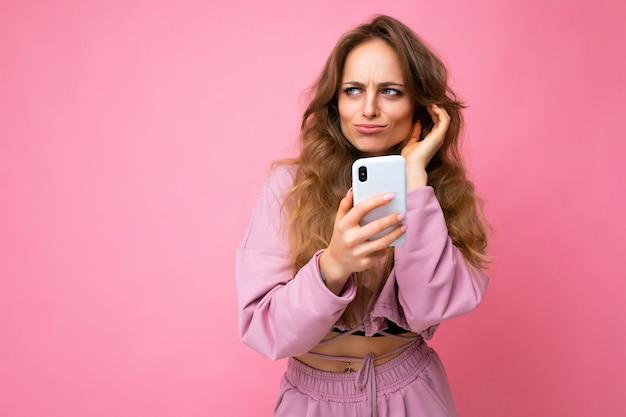 Bella giovane donna bionda sconvolta triste che indossa la felpa con cappuccio rosa isolata sopra la parete rosa con la copia